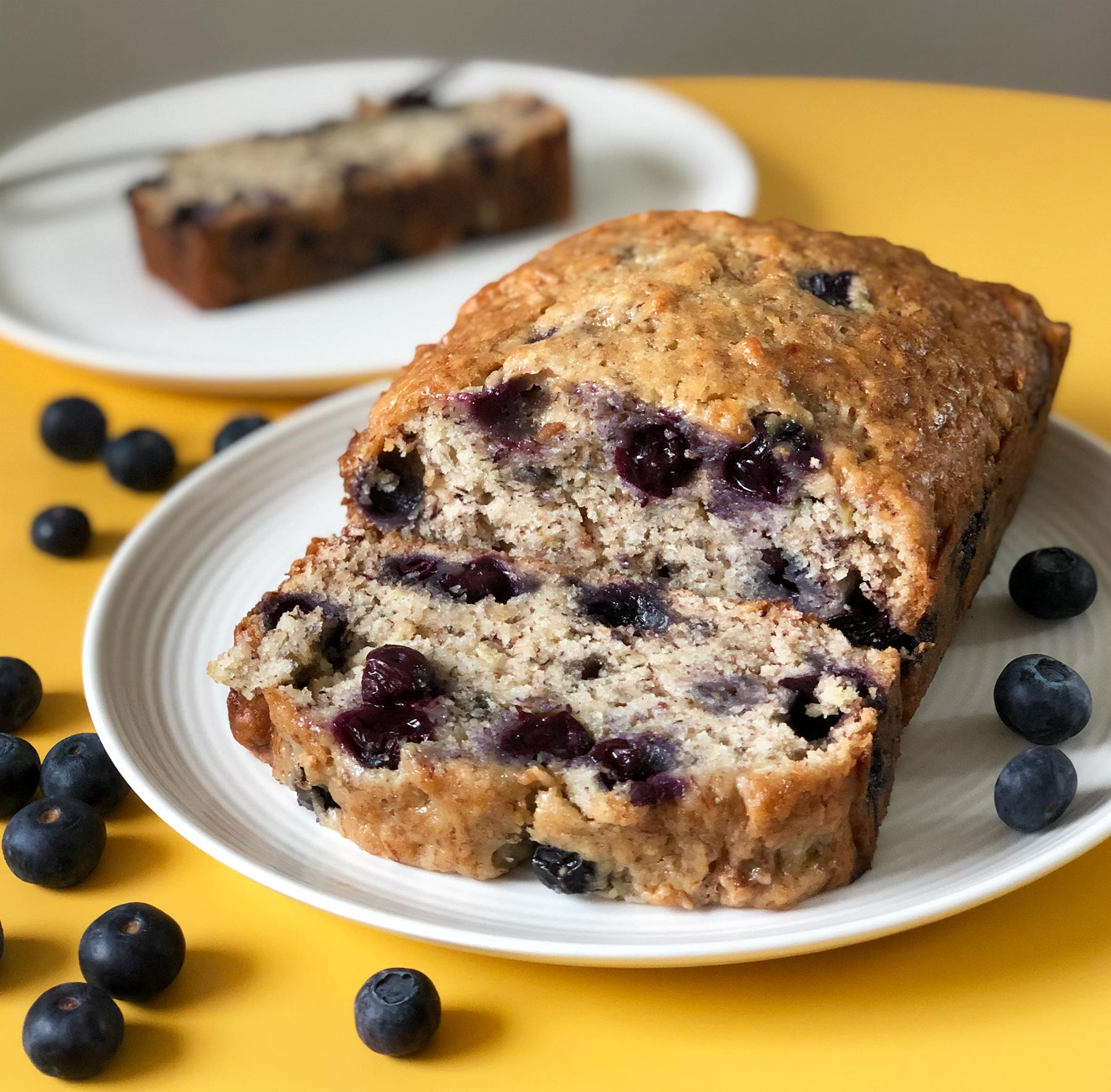 Banana bread with blueberries on a white plate and yellow table