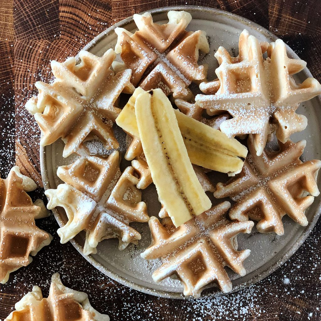 Mini banana waffles with sourdough starter on a plate, topped with banana slices.