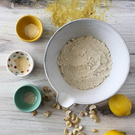 bowl of nut pulp ricotta with ingredients around it